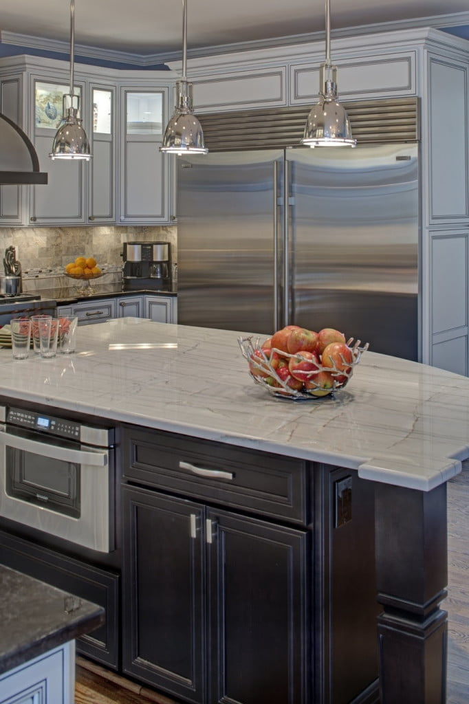 """The final kitchen features top-of-the-line finishes and appliances including separate refrigerator and freezer units by Sub-Zero, a 48"""" dual fuel Wolf range with integral grill, a custom stainless/oil-rubbed bronze hood, Bosch dishwasher with custom cabinetry panel, and a Sharp microwave drawer."""