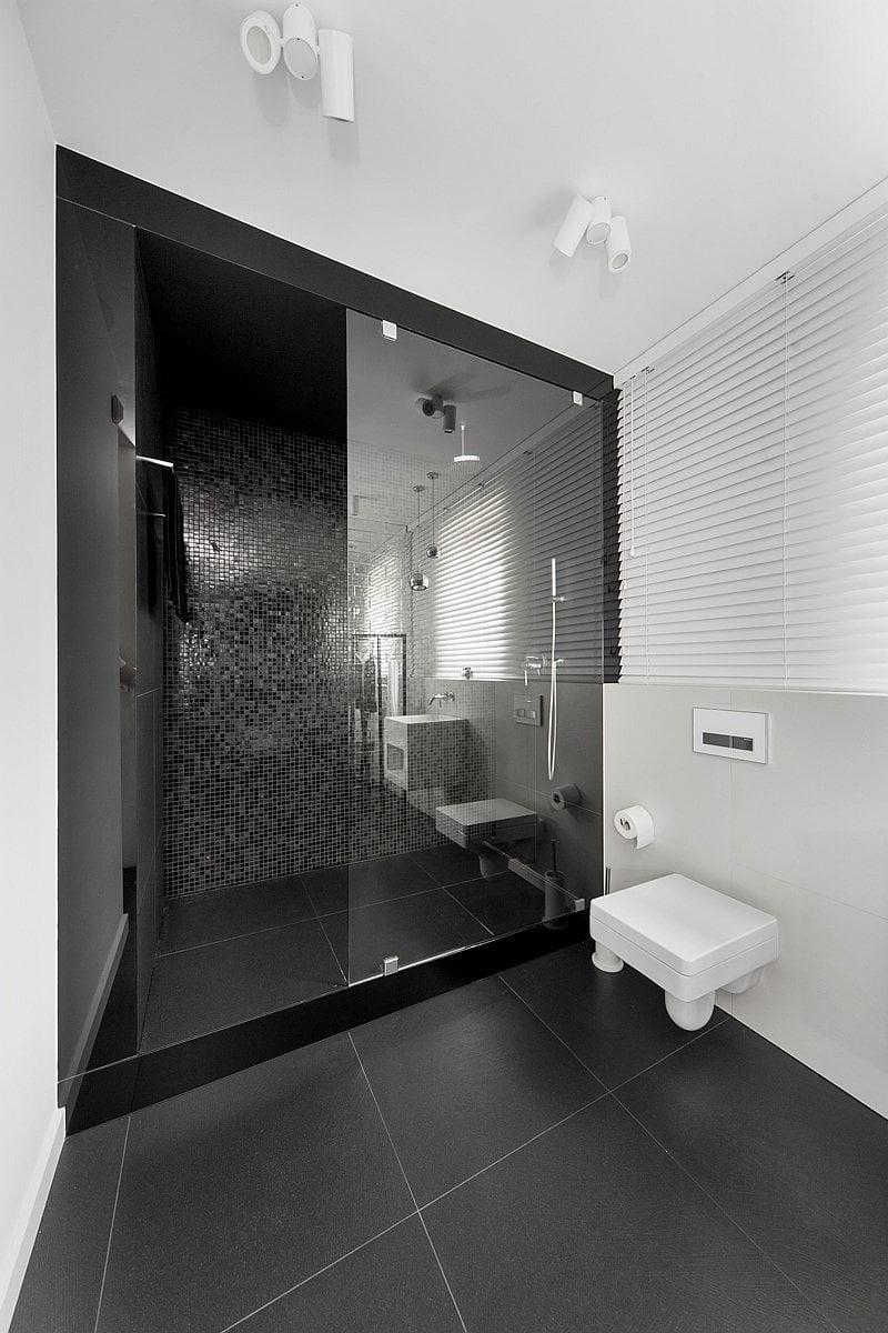 black and white bathroom is in a home in Mikolów, Poland, designed by Widawscy Studio Architektury