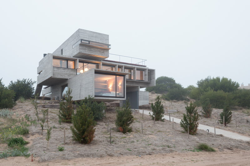 exposed concrete modern house with golfcourse view on cliff side