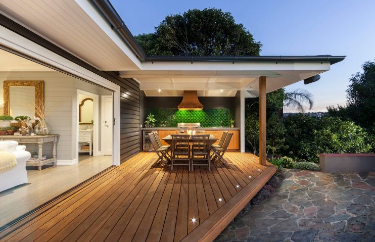 Floating outdoor deck design with covered patio in backyard of modern house