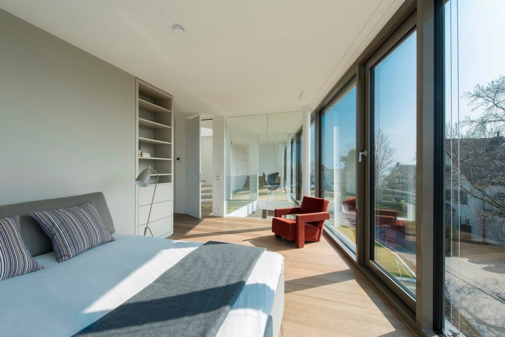 Full height hindge glass window with light shade furniture in bedroom