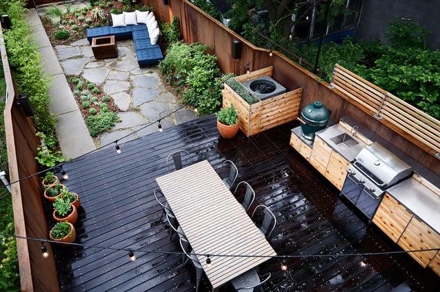 Outdoor deck flooring material is dark wood with backyard kitchen