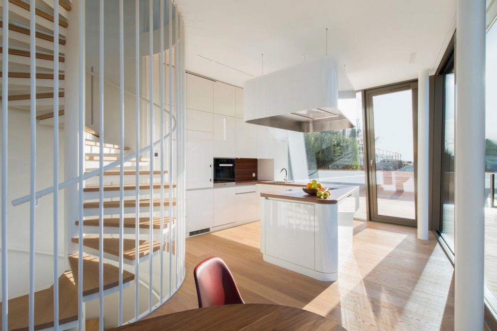 Steel spiral stair with wooden steps in modern house