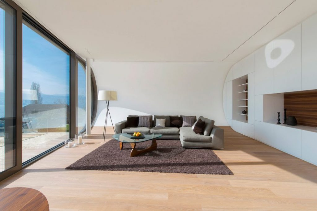 grey sofa seats with brown floor carpate on wooden floor and white color walls