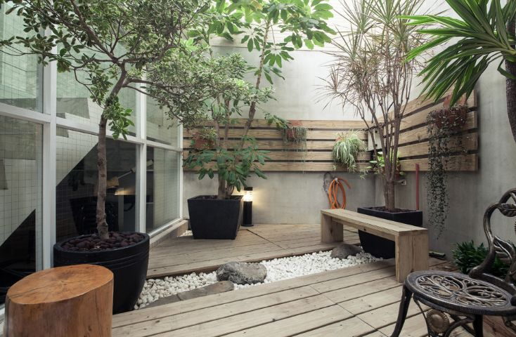 outdoor deck with river pabbles rocks and rustic furniture in small backyard
