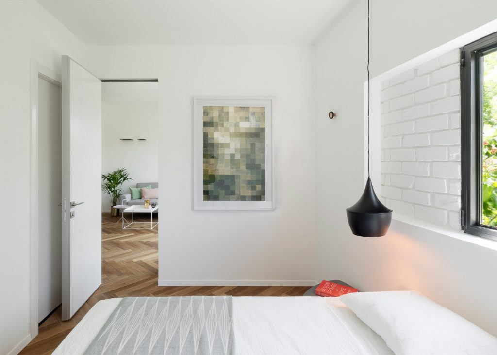 Bed Side Table Hanging Light and Painting in Modern Bedroom Decor.